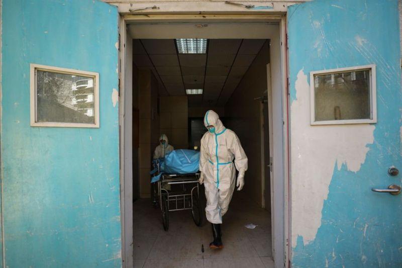 武汉两名医护人员正在搬运一名新冠肺炎患者的遗体。